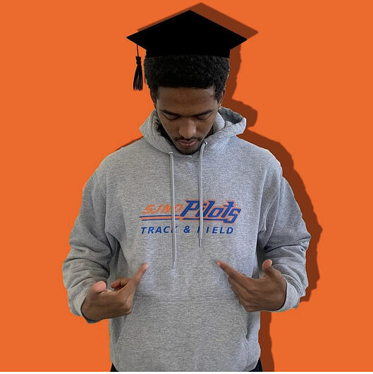 Alazar Hailu poses with his SJND track and field sweatshirt and graduation cap.