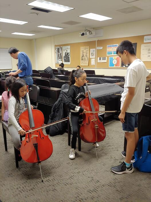 Issac Li assists younger students in their cello technique at the Laney Chinese Orchestra.