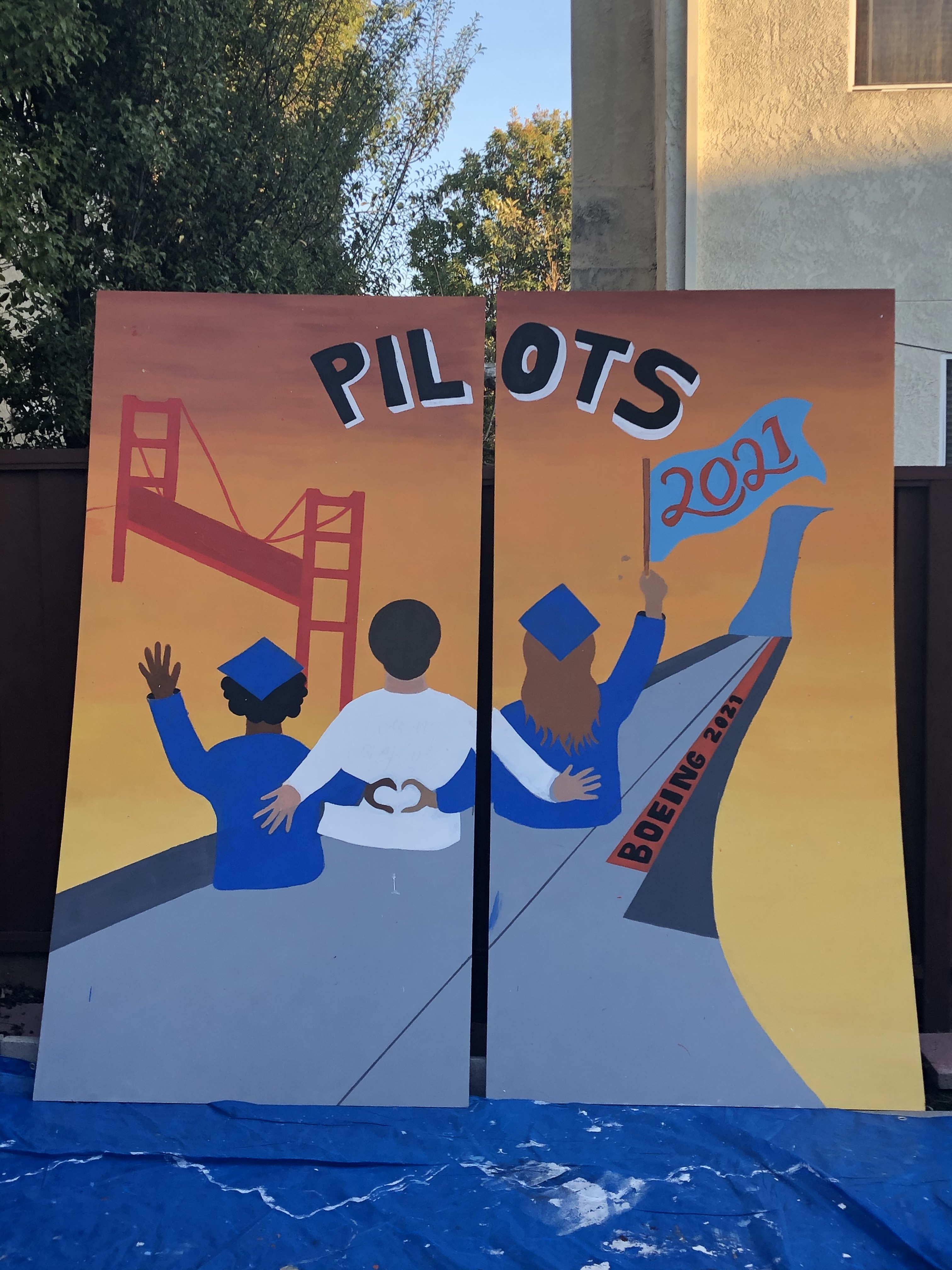 """The finished class of 2021 mural pictures three students sitting on the airplane wing of a """"Boeing 2021."""" They soar over the Golden Gate Bridge."""