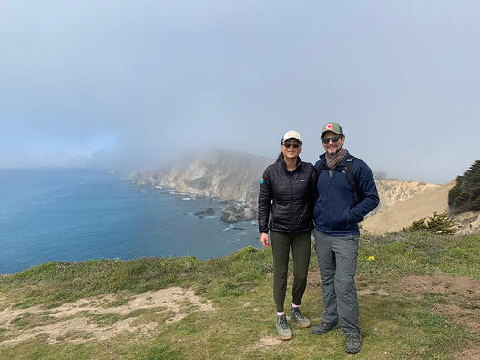 Anne and her husband out on a hike near the coast. The ocean and cliffs are shrouded in fog.