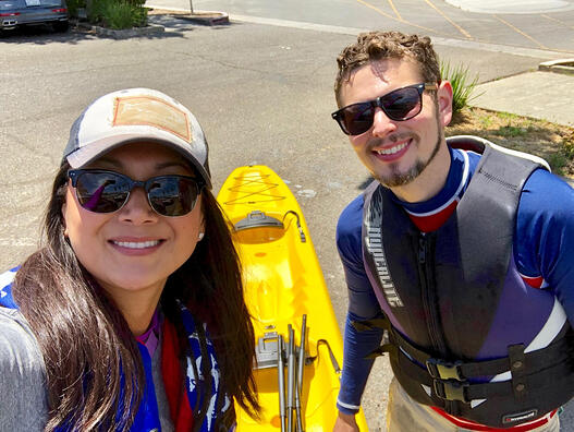 Anne and her husband take a selfie with their yellow kayak.