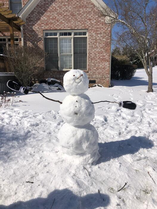 During the winter holidays, Rachel built a snowman with her siblings. It is sporting mittens and stands in front of a red brick home.