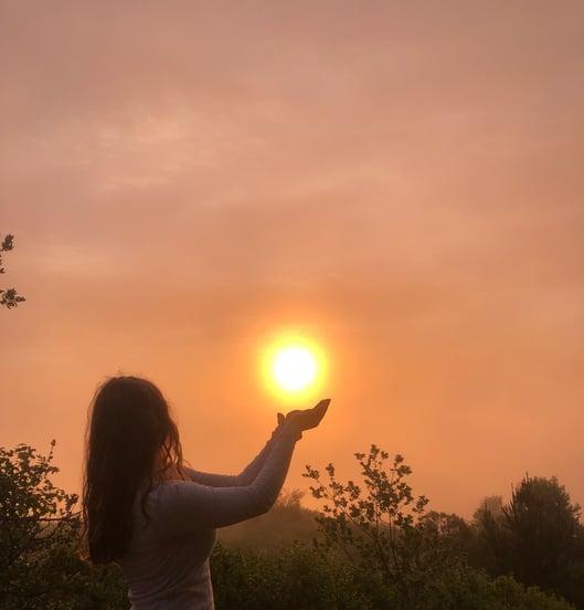 Rachel pretends to hold the sun at sunset. The sky is sherbert orange.