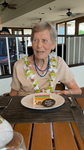 Violet Golden celebrates her 100th birthday with a slice of rainbow cake and a Hawaiian lei at a restaurant.
