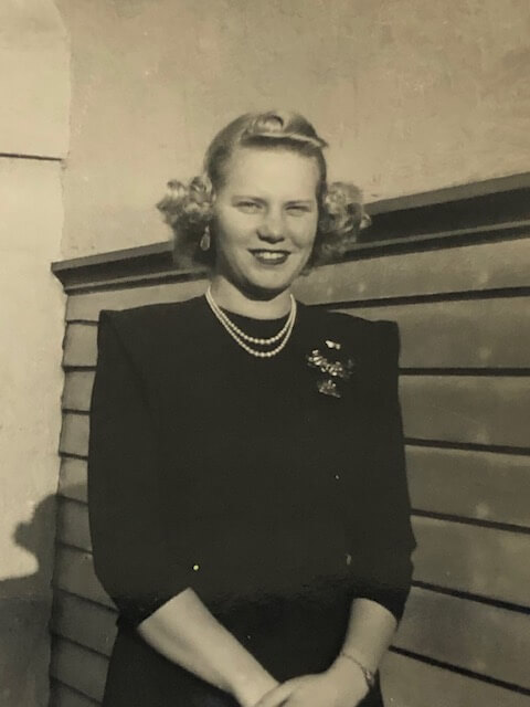 Violet Golden, SJND '39, smiles for the camera wearing a black long-sleeve dress and a string of pearls.